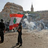 A protester waves the national flag during clashes with security forces in downtown Beirut on Saturday.  | AFP-JIJI