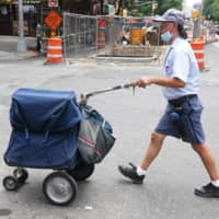 A U.S. Postal Service worker walks with his cart in New York City.  | REUTERS