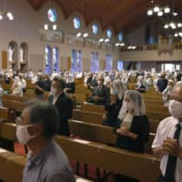 People attend mass held in memory of bomb victims at Urakami Church to mark the 75th anniversary of the atomic bombing of Nagasaki, in the city on Sunday. | KYODO