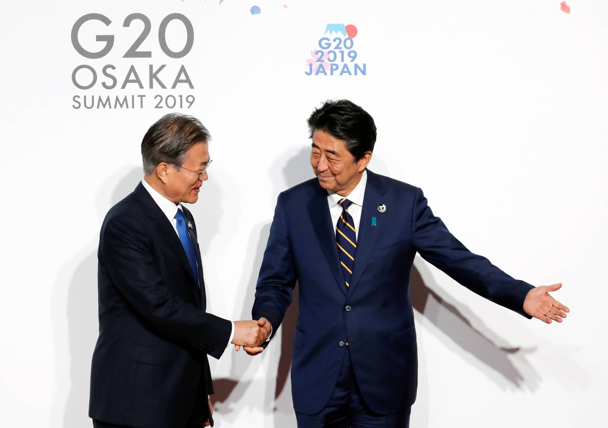 South Korean President Moon Jae-In is welcomed by Prime Minister Shinzo Abe upon his arrival at the Group of 20 leaders summit in Osaka in June 2019.   POOL / VIA REUTERS