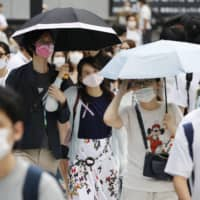 People visit Tokyo's Shibuya district amid a scorching hot summer day on Saturday. | KYODO