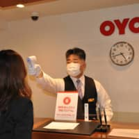 An employee at Oyo Hotel New Washington in Tokyo checks the body temperature of a guest as part of the facility's anti-coronavirus measures on July 27. | KYODO