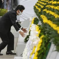 Never forget: Prime Minister Shinzo Abe lays a floral tribute in Hiroshima's Peace Memorial Park on the 75th anniversary of the atomic bombing. | KYODO