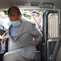 Hong Kong media tycoon Jimmy Lai, who founded local newspaper Apple Daily, gets into a car after being arrested by police officers at his home in Hong Kong on Monday. | AP