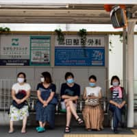 People wearing face masks wait at a tram station in Tokyo. The capital confirmed 197 new infections Monday.