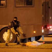 A law enforcement officer gestures next to a man laying on the ground during clashes with opposition supporters after polls closed at the presidential election in Minsk on Sunday. | REUTERS