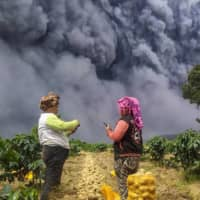 Farmers harvest their potatoes as Mount Sinabung erupts on Monday.  | ANTARA FOTO / VIA REUTERS