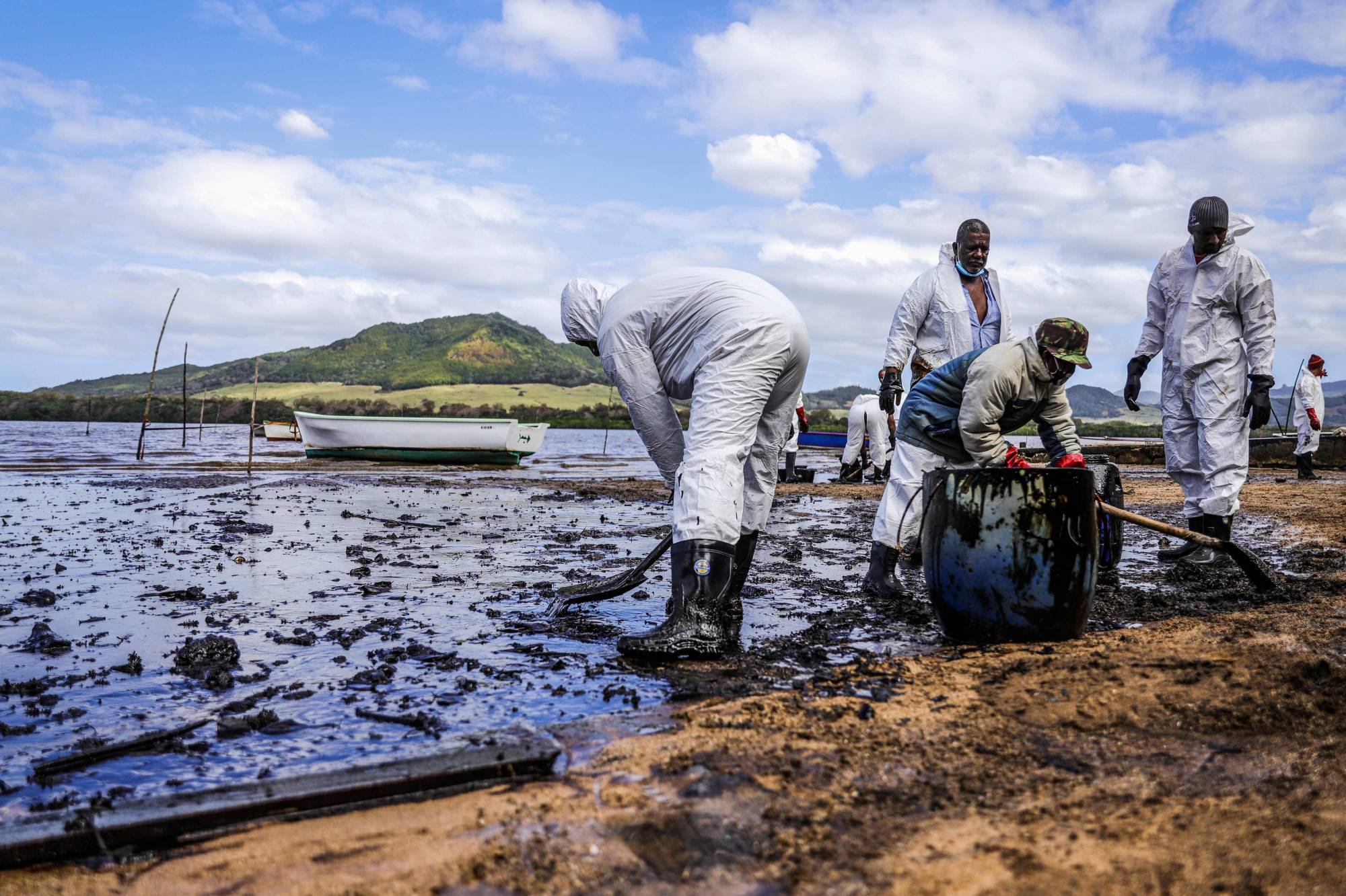 People scoop leaked oil from the vessel MV Wakashio, near Blue bay Marine Park in southeast Mauritius on Sunday.   | L'EXPRESS MAURICE / VIA AFP-JIJI