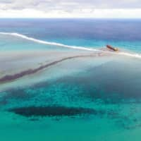 A large patch of leaked oil and the vessel MV Wakashio off the coast of southeast Mauritius on Thursday | AFP-JIJI