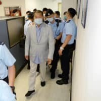 Media mogul Jimmy Lai is escorted by police at the Apple Daily office in Hong Kong on Monday.  | APPLE DAILY / VIA REUTERS