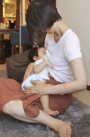 A mother breast-feeds her child in Tokyo last week. Concern over transmission of the virus via breastfeeding is widespread but health bodies differ in their approach to the issue and the level of risk they attach to it. | KYODO