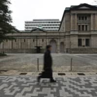 A pedestrian walks past the Bank of Japan headquarters in Tokyo. | BLOOMBERG