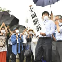 Plaintiffs and supporters cheer after the Hiroshima District Court ruled in favor of their claim over 'black rain' on July 29. | KYODO