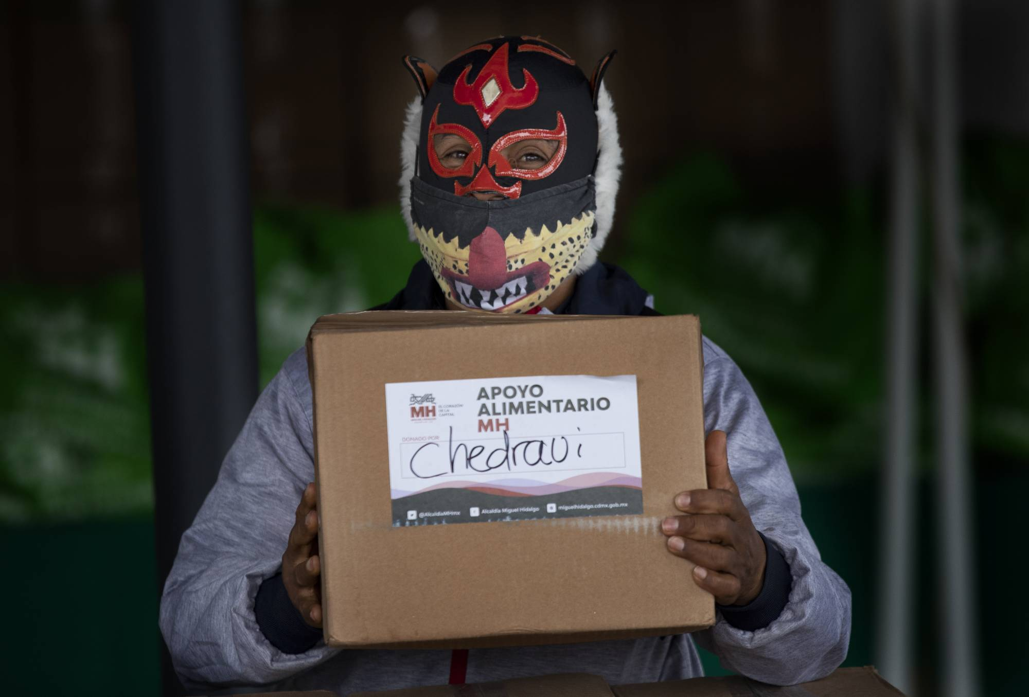 Mexican Lucha Libre wrestler 'Pequeno Felino' stands ready to handout a food parcel donated by a local supermarket, to his fellow wrestlers, who have fallen on hard times due to the new coronavirus pandemic, on Aug. 3 in Mexico City. | AP