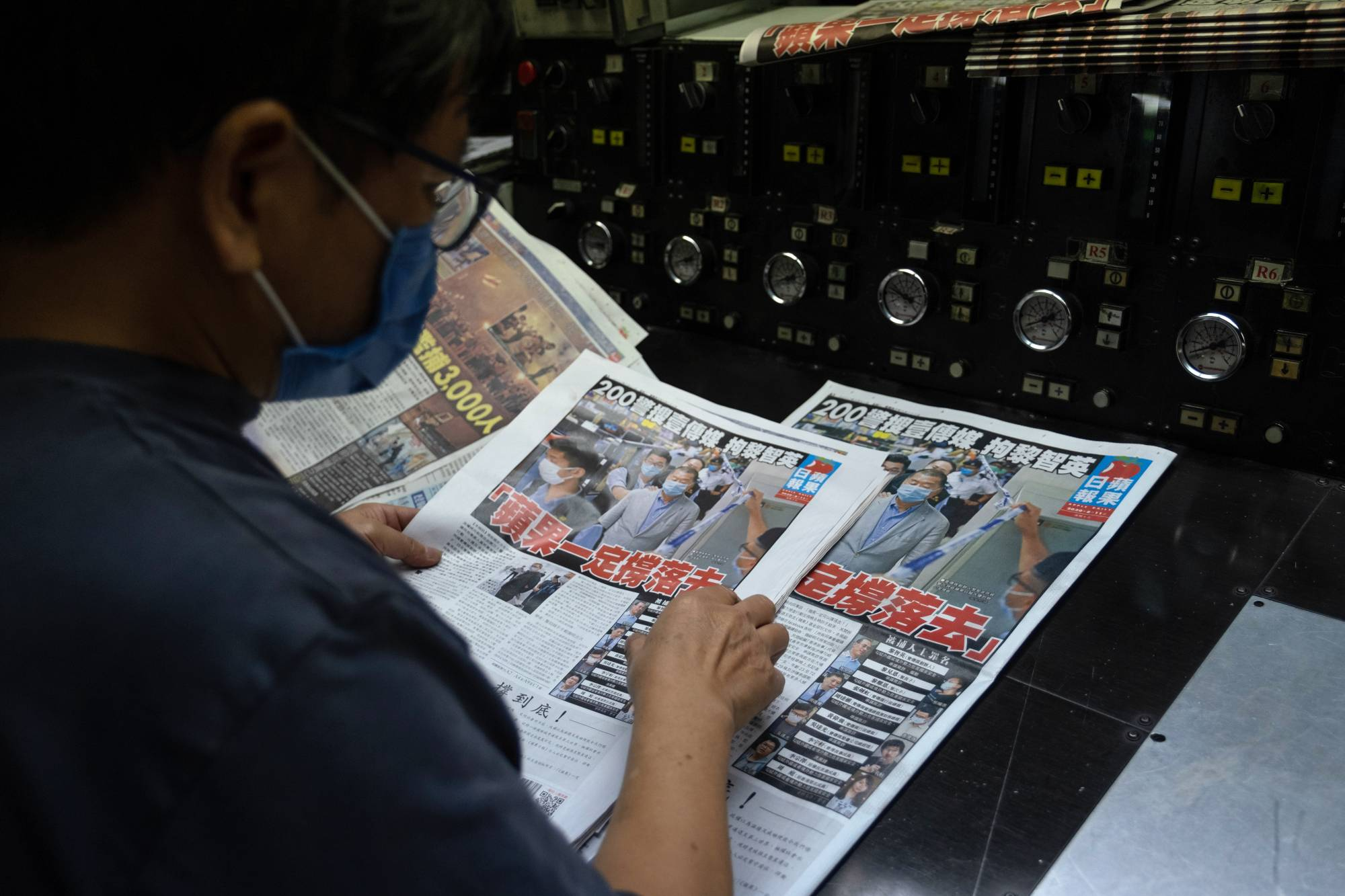 An employee inspects the front page of the Apple Daily newspaper, published by Next Digital Ltd., at the company's printing facility in Hong Kong on Tuesday. Hong Kong police arrested Next Digital Chairman Jimmy Lai on Monday and raided the offices of his flagship newspaper the Apple Daily. | BLOOMBERG
