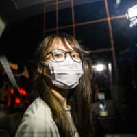 Prominent Hong Kong pro-democracy activist Agnes Chow looks out of a car window while being driven away by police from her home after she was arrested under the new national security law in the city late Monday.