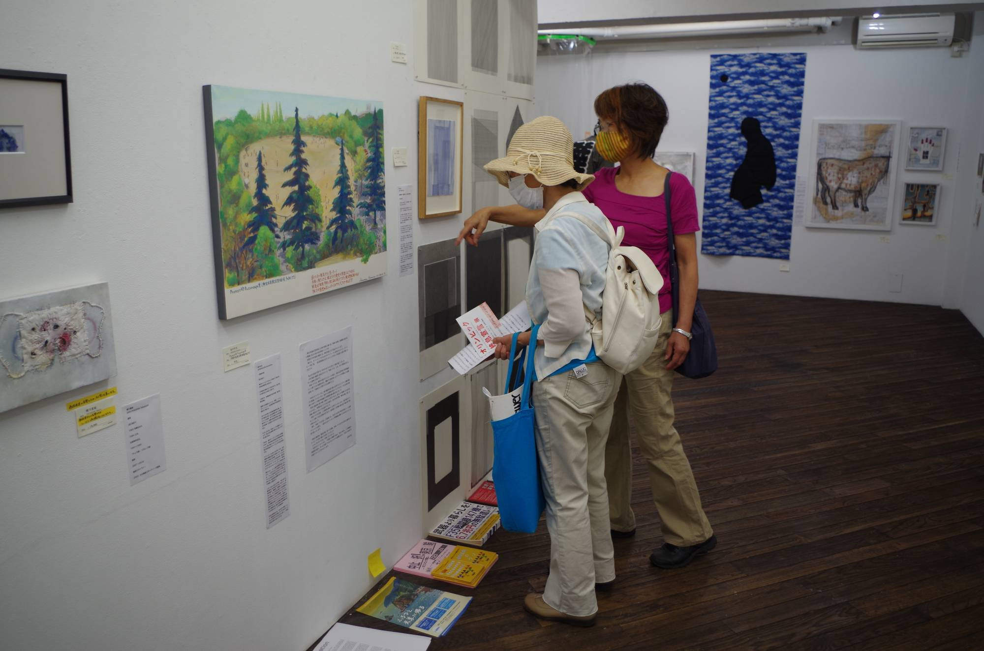Not in our backyard: Visitors look at a painting by Munemitsu Shimamura at an exhibition held by an anti-Olympics artists group in Tokyo.  | KYODO