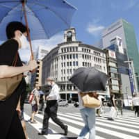 People walk in Tokyo's Ginza district on Tuesday, with many holding parasols under a glaring sun. | KYODO
