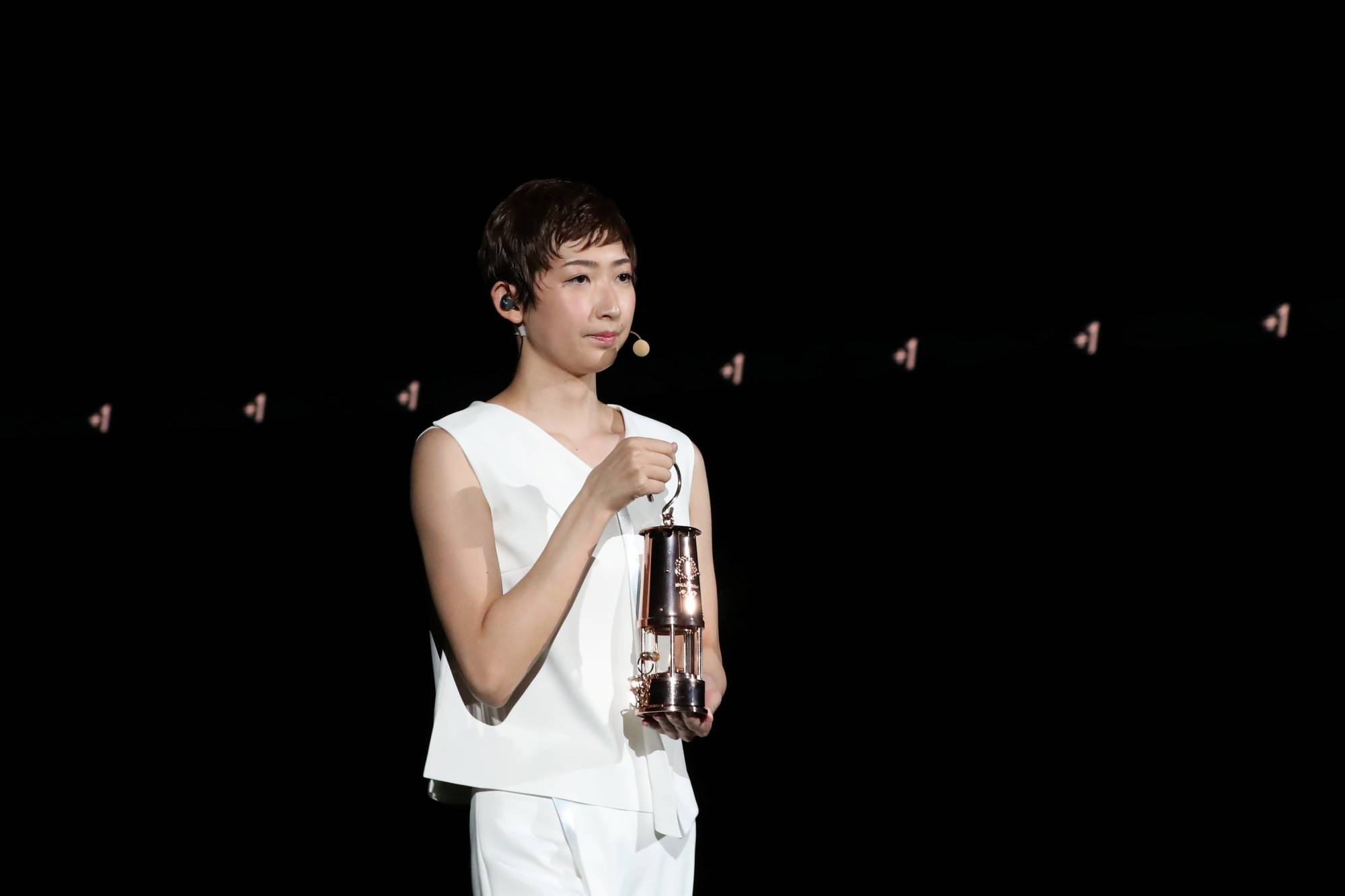 Rikako Ikee holds a lantern containing the Olympic flame during an event marking the one-year countdown to the postponed 2020 Tokyo Olympics on July 23 at Tokyo's National Stadium. | POOL / VIA REUTERS