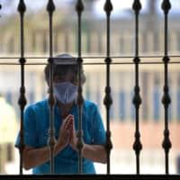 A believer prays outside the Parish Cathedral Jesus Christ Our Peace during a pilgrimage in Soacha municipality near Bogota, Colombia, on Monday. The novel coronavirus pandemic chalked up another grim milestone this week as the world surpassed 20 million recorded cases of infection. | AFP-JIJI