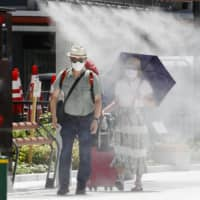 People walk through a mist shower on Tuesday in the Ginza district of Tokyo. In the city center, temperatures started soaring early in the morning and had already hit 30 degrees Celsius by 7 a.m. | KYODO