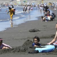 People cool off at Shonan Beach amid scorching summer heat in Fujisawa, Kanagawa Prefecture, on Tuesday. | AP