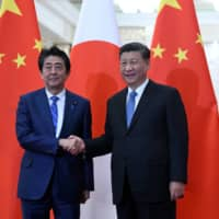 Chinese President Xi Jinping, shown meeting Prime Minister Shinzo Abe in December, calls united front work a 'magic weapon' for advancing Chinese Communist Party goals. | REUTERS