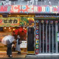 Customers stand in front of a bubble tea shop next to the Robot Restaurant, temporarily closed due to the coronavirus, in the Shinjuku district of Tokyo on April 1. | BLOOMBERG