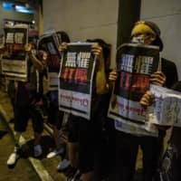 Supporters hold copies of the Apple Daily newspaper as Hong Kong pro-democracy media mogul Jimmy Lai is released on bail Wednesday.  | AFP-JIJI