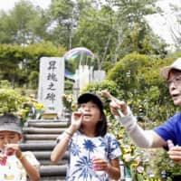 Members of the bereaved families of the victims of the 1985 Japan Airlines jetliner crash visit the site where it went down in Ueno, Gunma Prefecture, on Wednesday, the 35th anniversary of the accident that killed 520 passengers and crew. | KYODO