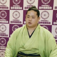 Newly promoted jūryō wrestler Nishikifuji (right), along with his stablemaster Isegahama, speaks during an online news conference on Aug. 5 in Tokyo's Ryogoku Kokugikan. | JAPAN SUMO ASSOCIATION / VIA KYODO