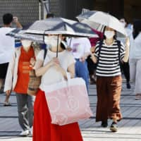 People shield themselves from the sun and the new coronavirus in Hachioji, Tokyo, on Tuesday. | KYODO