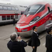 People take pictures of a Frecciarossa 1000 high-speed train by Bombardier Transportation at the InnoTrans railway technology trade fair in Berlin in September 2014. | REUTERS