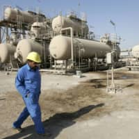 An Iraqi worker walks in front of an oil refinery in North Rumaila oilfield in Basra in January 2009. Japanese engineering company JGC Holdings Corp. said Wednesday that it has won a contract to renovate a refinery in the Iraqi city. | REUTERS