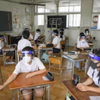 Hot in here: Students wear face shields and masks during a class to prevent the spread of coronavirus. However, critics say the students are at risk of heatstroke due to the measures.  | KYODO