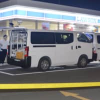 Investigators examine the Lawson convenience store in Utsunomiya, Tochigi Prefecture, where a store clerk was stabbed to death Wednesday. | KYODO