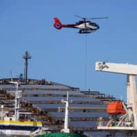 A helicopter flies above the bulk carrier ship MV Wakashio, which has ran aground on a reef off Mauritius. | REUTERS