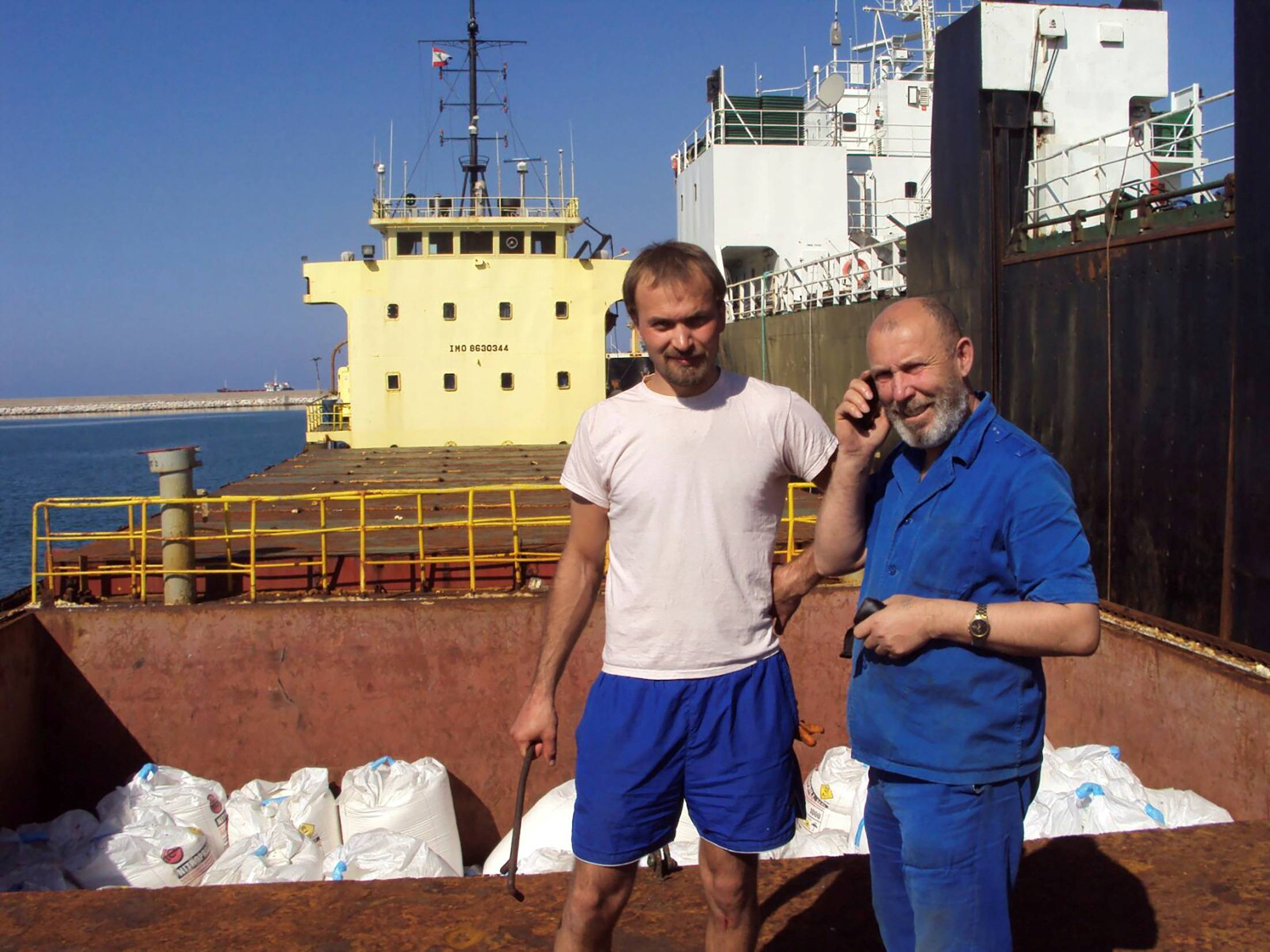 Boris Prokoshev (right), captain of the cargo vessel Rhosus, and boatswain Boris Musinchak pose next to a freight hold loaded with ammonium nitrate in the port of Beirut, Lebanon, in 2014. | REUTERS