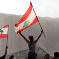 Demonstrators wave Lebanese flags during protests on Tuesday near the site of the blast in Beirut's port area.  | REUTERS