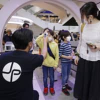 Children have their temperatures checked at the entrance to the Tokyo Joypolis indoor amusement park in June. | KYODO