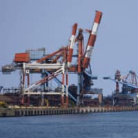 A cargo ship sits at a Nippon Steel Corp. plant in Kashima, Ibaraki Prefecture in April as falling steel demand sent the nation's top three steelmakers into the red during the first quarter. | BLOOMBERG