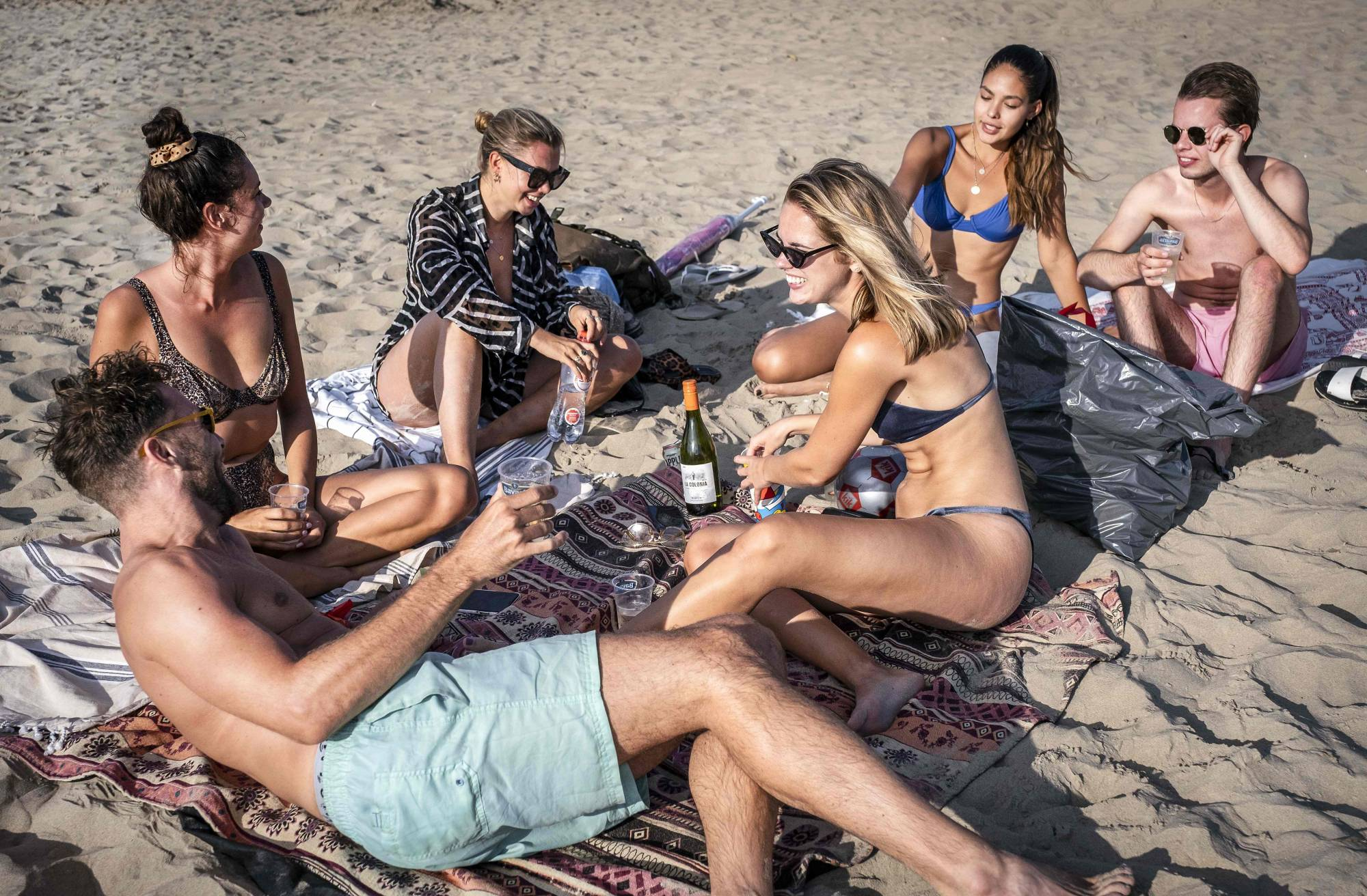 A group of young people gather on the beach in the Dutch coastal town of Zandvoort on Aug. 6. That day Prime Minister Mark Rutte called on tourists to avoid crowded places in Amsterdam as coronavirus infections showed a worrying rise. | AFP-JIJI