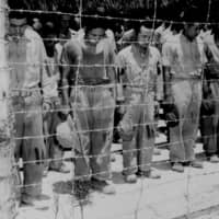Japanese prisoners of war in Guam react with bowed heads after hearing Emperor Hirohito deliver the announcement of Japan's unconditional surrender on Aug. 15, 1945. | U.S. NATIONAL ARCHIVES / VIA REUTERS