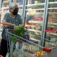 A woman looks at frozen food products in a Beijing supermarket. Viruses can survive up to two years at temperatures of minus 20 degrees Celsius, but scientists and officials say there is no strong evidence so far the coronavirus can spread via frozen food. | REUTERS