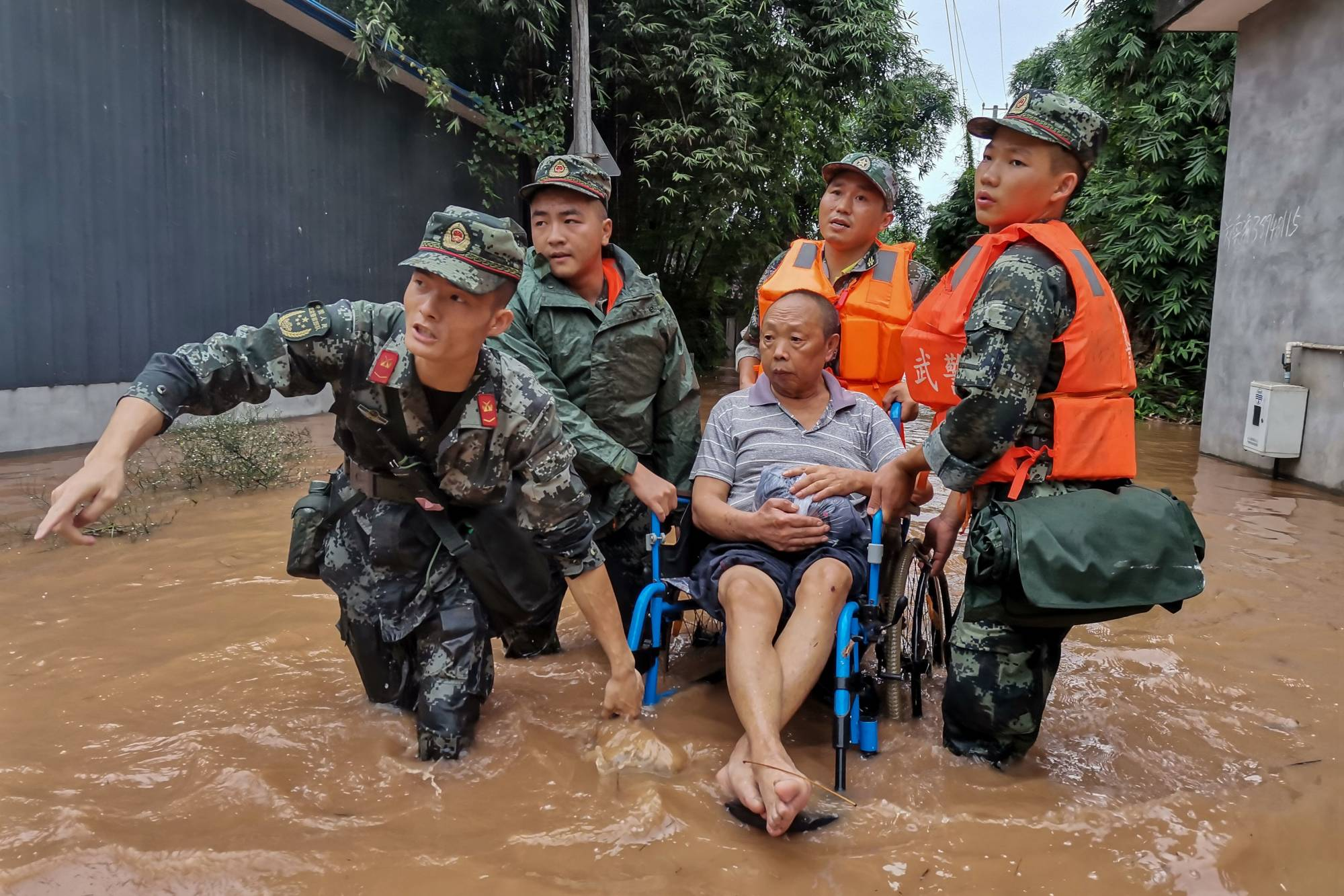 China's paramilitary police officers evacuate a resident on a flooded street in Meishan in Sichuan province. While dams and levees have helped save lives, flooding remains China's biggest natural headache. | AFP-JIJI