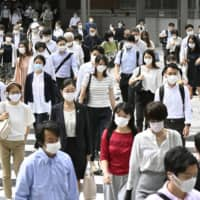 People commute to work in the Marunouchi district near Tokyo Station last month. | KYODO