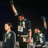 Australian sprinter Peter Norman (left) was sanctioned by the Australian Olympic Committee for his role in the podium protests of U.S. runners Tommie Smith (center) and John Carlos after the 200 meter final in Mexico City on Oct. 16, 1968. Australian lawmakers issued a posthumous apology to Norman in 2012. | AP