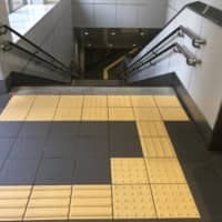 Tactile paving can guide a visually impaired person to the top of a flight of stairs at a train station in Tokyo. | KATHRYN WORTLEY