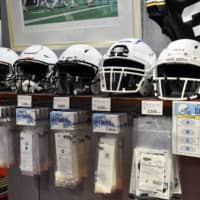 Helmets fitted with various face shields are seen on display at a QB Club shop in Tokyo's Shibuya district. | HIROSHI IKEZAWA