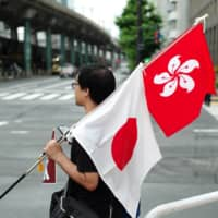 The flags of Japan and Hong Kong are displayed at a Hong Kong pro-democracy demonstration in Tokyo in June last year. | RYUSEI TAKAHASHI